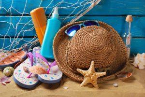 Como protegerse del sol adecuadamente. Imagen de un de un sombrero sobre la arena de la playa con unas chanclas y protectores solares